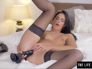 Shaved beauty pushes a big black dildo inside