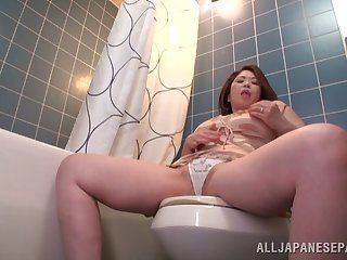 Solo mature Natsuko Kayama spreads her legs to masturbate in the bathroom